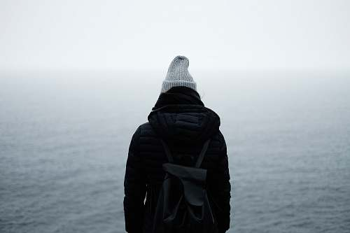 photo people person wearing black jacket standing in front of the ocean backpack free for commercial use images