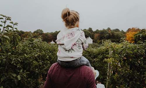 people photo of girl riding on person shoulder human