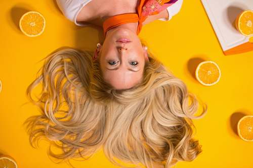 people photo of woman leaning on yellow surface blonde