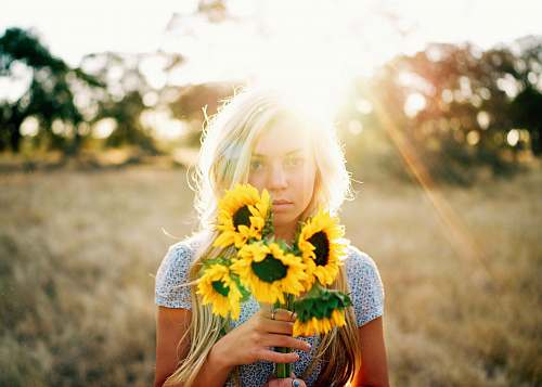 woman portrait photography of woman holding bouquet of sunflowers people