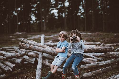 human selective focus photography of boy and girl sitting on log people