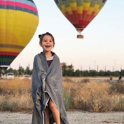 people selective focus photography of girl covered by gray scarf with background of hot air balloons human