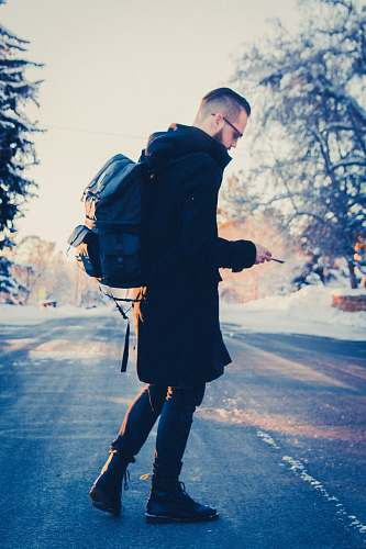 human selective focus photography of man in black coat carrying gray backpack people