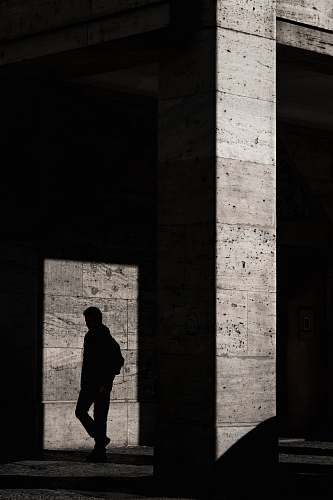 human silhouette of man standing inside structure people