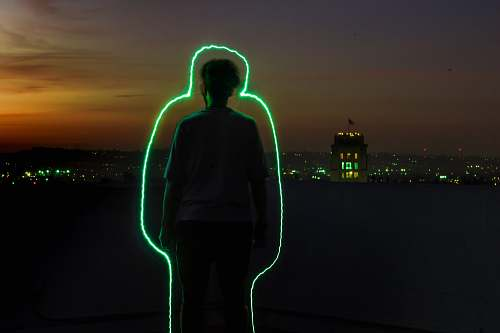 people silhouette of man standing with green neon outline during sunset human
