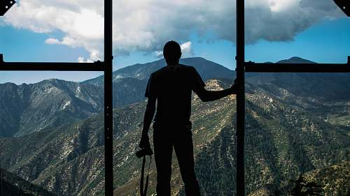 human silhouette photo of person standing near door overlooking mountain during daytime people