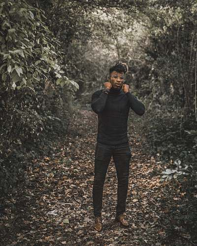 people standing man wearing black turtleneck sweater and black fitted pants surrounded with trees during daytime human