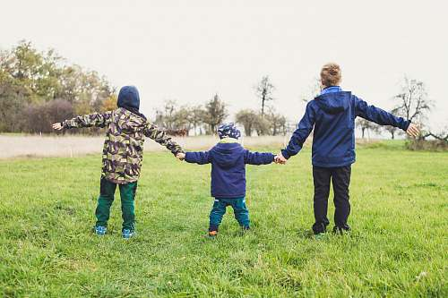 human three children holding hands standing on grasses people
