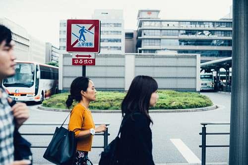 human three people walking beside metal rails people