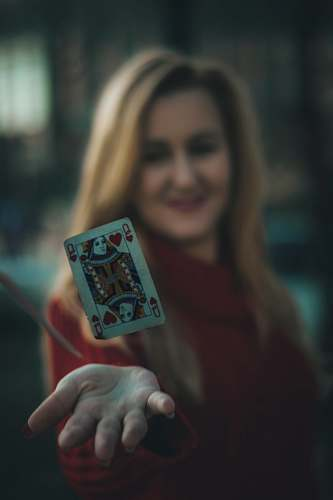 human time lapse photo of queen of hearts playing card near woman's palm people