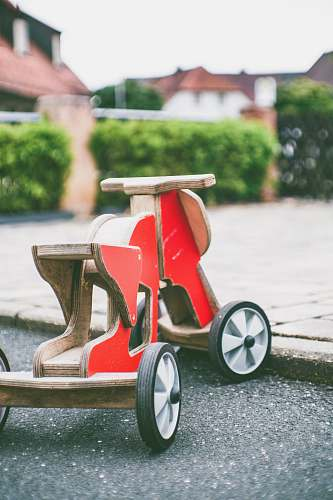 people toddler's red and brown wooden ride-on toy on concrete pavement human