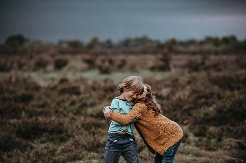 human two child hugging in front of field people