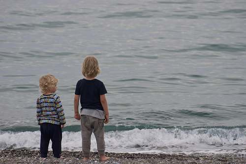 human two child standing on shore people