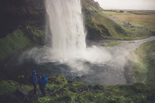 people two person wearing blue hoodie standing on ground in front of waterfalls human