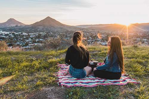 people two women having picnic facing mountain and buildings during golden hour human
