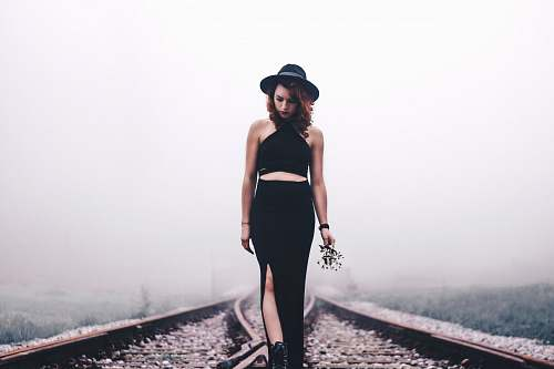 human woman holding flowers looking on train rails people