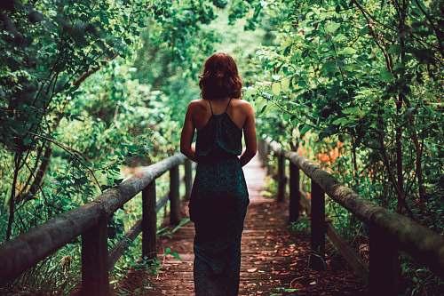 people woman in black dress standing on bridge human