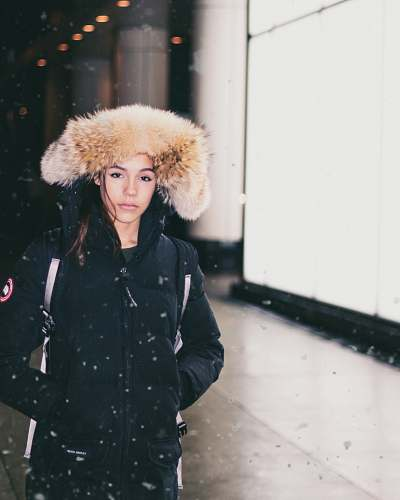 people woman in black parka jacket standing while snowing human