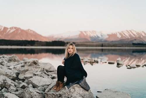 human woman in black sitting on rock near lake people