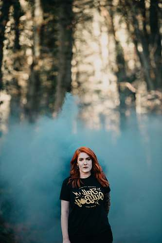 human woman in black t-shirt with teal smoke in selective focus photography people