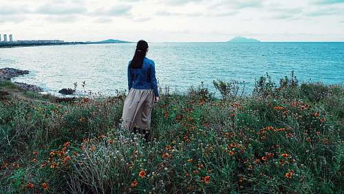 people woman in blue blouse and gray skirt standing on red flower field beside body of water during daytime human