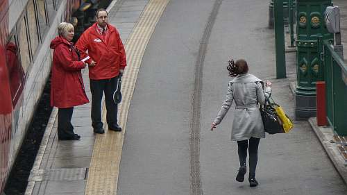 people woman in gray coat walking on the road during day time human