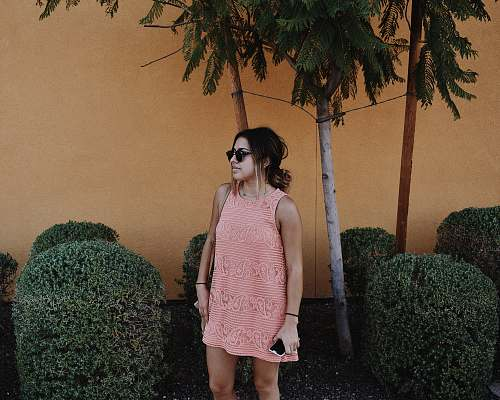 people woman in pink sleeveless shift mini dress standing near bushes at daytime human