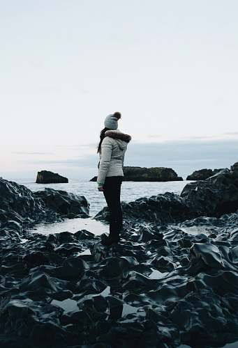 photo people woman in white parka jacket and black pants outfit standing on rocks near body of water under white sky at daytime human free for commercial use images