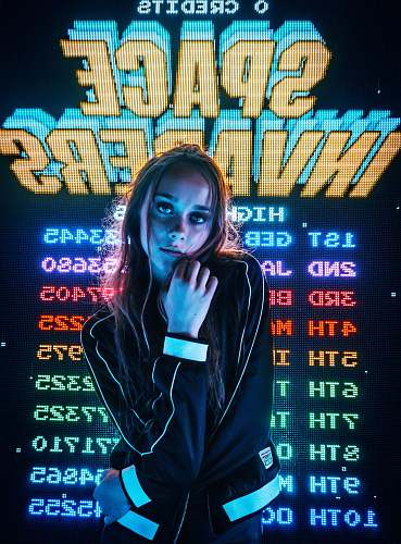 people woman posing for photo in front of Space Invaders scoreboard human
