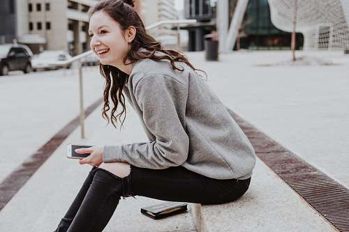 people woman sits on sidewalk holding smartphone while smiling human