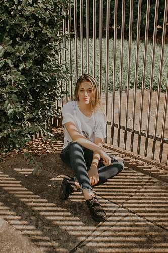 people woman sitting beside green bush and gray metal gate human