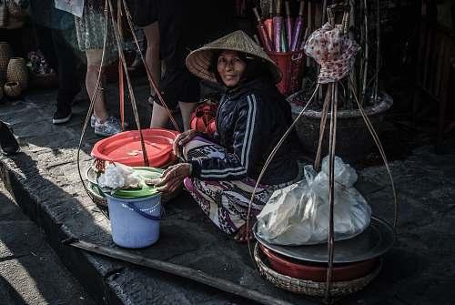people woman sitting beside street bucket human