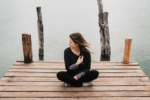 human woman sitting on dock during daytime people
