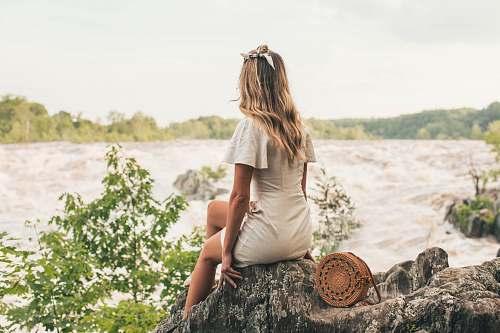 people woman sitting on rock beside body of water human