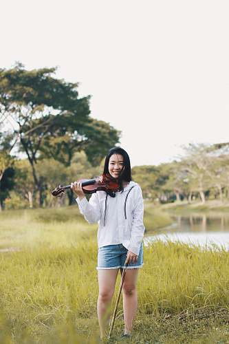 human woman standing holding violin near river people