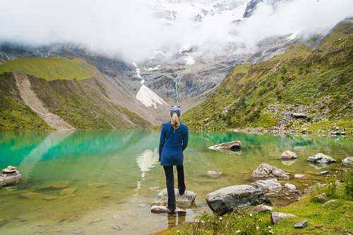 human woman standing in front of body of water and mountain people