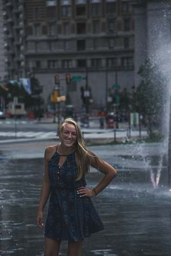 human woman standing in front of outdoor fountain people