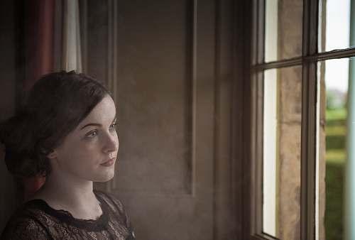 people woman standing near window looking outside human