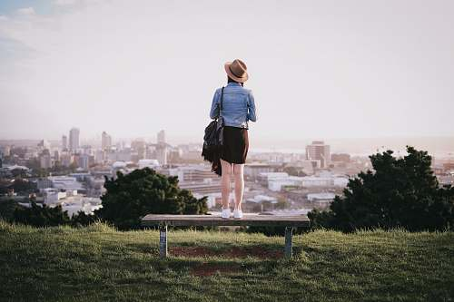 people woman standing on bench facing city skyline during daytime human