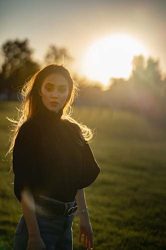 human woman standing on green grass during golden hour people