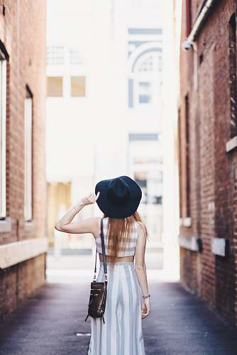 people woman standing on pathway holding hat human
