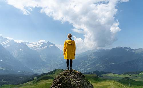 people woman standing on rock in front of mountain during daytime human