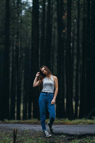 human woman standing on walkway in front of forest trees people