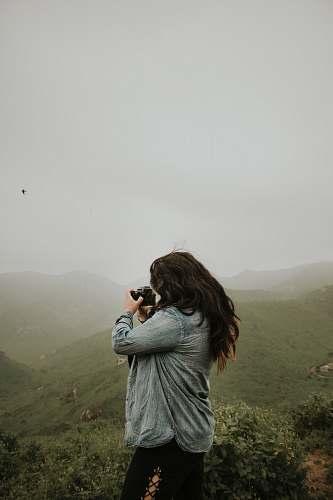 human woman taking photo of mountain during daytime people