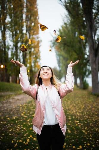 human woman throwing leaves during daytime people