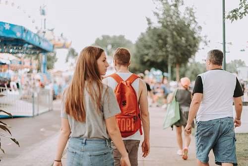 human woman walking near two men in pathway during daytime people