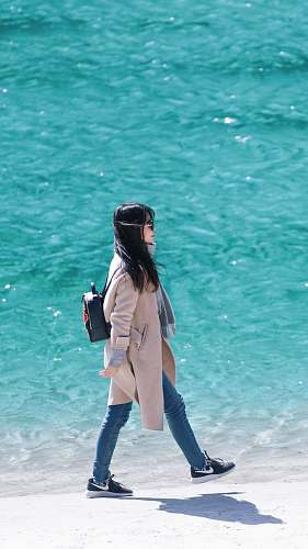 people woman walking on seashore wearing coat human