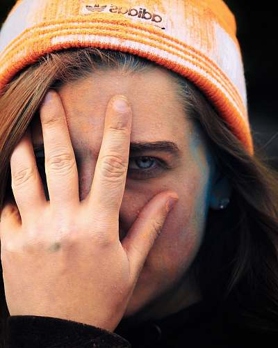 human woman wearing adidas cap holding her face people
