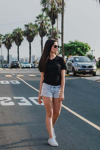 human woman wearing black V-neck shirt and blue shorts standing on gray concrete road people