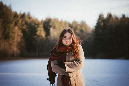 people woman wearing brown coat and red scarf human
